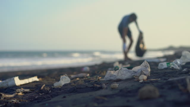 Young man clean up the beach from a trash