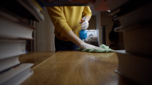 Young man cleaning table with disinfection spray