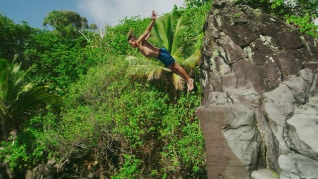 若い男クリフダイビング - 崖点の映像素材/bロール