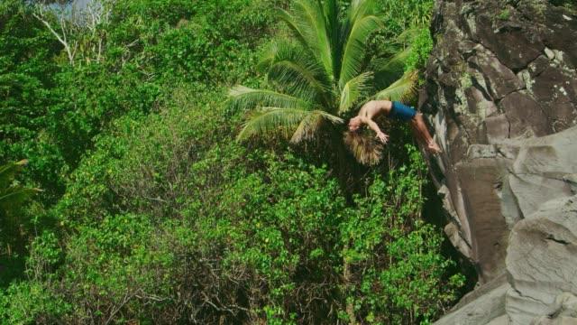 若い男クリフジャンプ backflipping - 崖点の映像素材/bロール