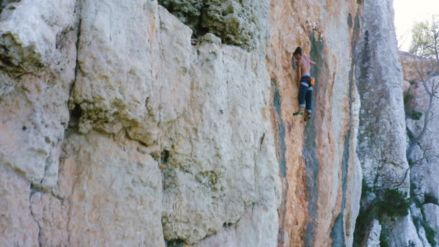A young man climber ascends vertical rock. 4K