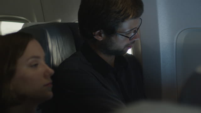 Young man closes a window shade on an airplane while a woman sits next to him. video