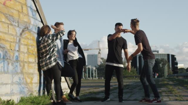 若い男来ると屋外のティーンエイ ジャーの友人たちの挨拶グループ - street graffiti点の映像素材/bロール