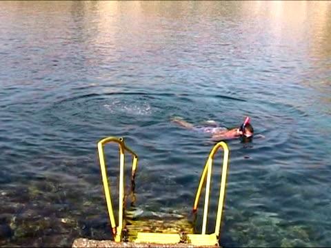 vídeos de stock, filmes e b-roll de jovem a partir do fora da água após o mergulho livre - equipamento de esporte aquático