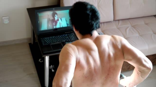 en ung man bedriver online-utbildning hemma. visar motion dips skytte för webbkamera av den bärbara datorn. fjärrarbete under karantänen. överst vyn. - balettstång bildbanksvideor och videomaterial från bakom kulisserna