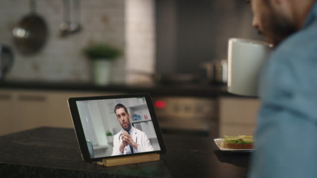 young man consults online doctor by using tablet while sitting at the kitchen table. - video call video stock e b–roll