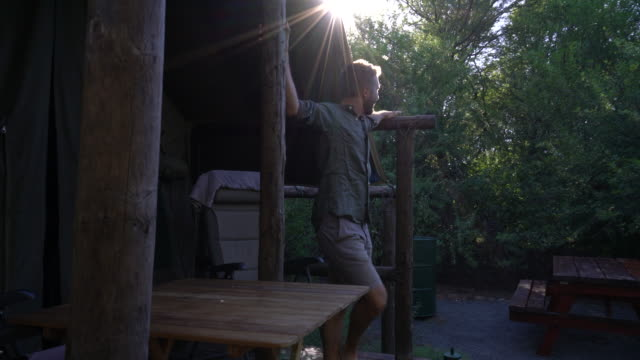 Young man contemplating nature from wooden lodge video