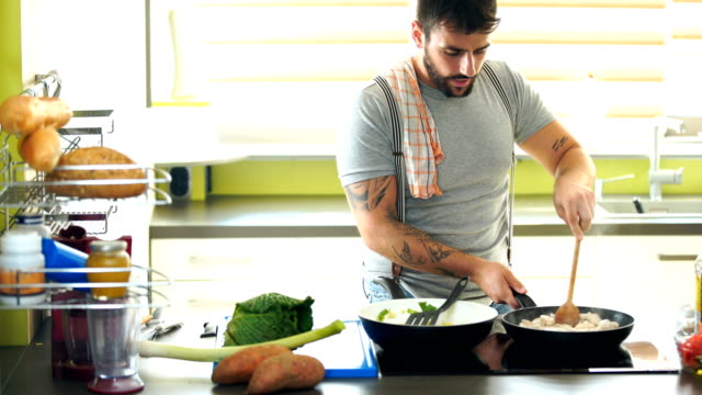 young man cooking at home. - articoli casalinghi video stock e b–roll