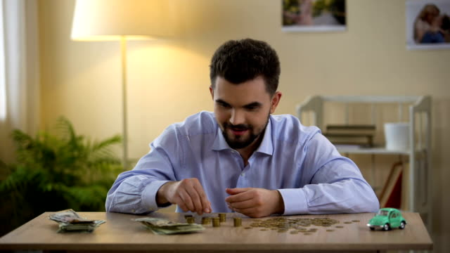 Young man counting money and looking at toy car, savings for purchase, dream Young man counting money and looking at toy car, savings for purchase, dream house rental stock videos & royalty-free footage