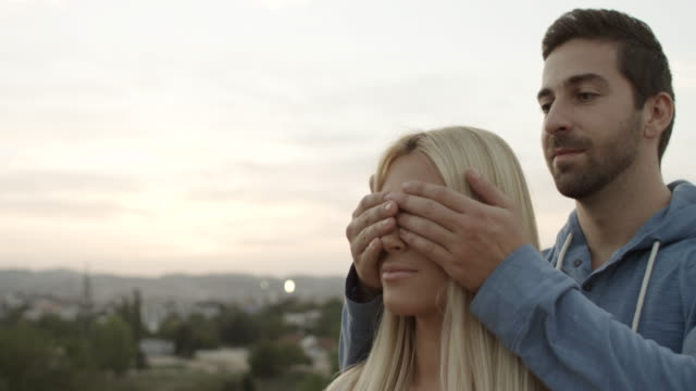 Young man covering the eyes of surprised girlfriend video