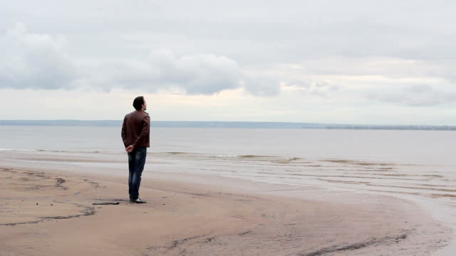 Young man crouching by the sea video