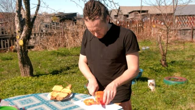 vídeos de stock, filmes e b-roll de jovem cortes pimenta vermelha na placa. preparação de sanduíches. - camiseta preta
