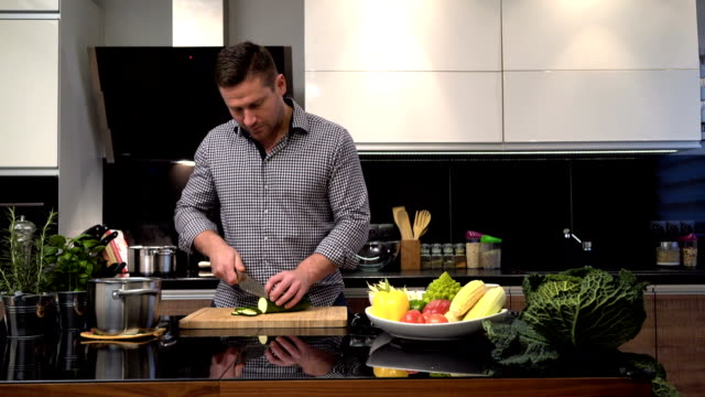 young man schneiden zucchini. schieberegler erschossen. - glutenfrei stock-videos und b-roll-filmmaterial