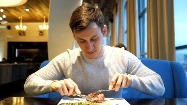 young man cutting meat beef steak eating enjoying dinner in restaurant - stek filmów i materiałów b-roll