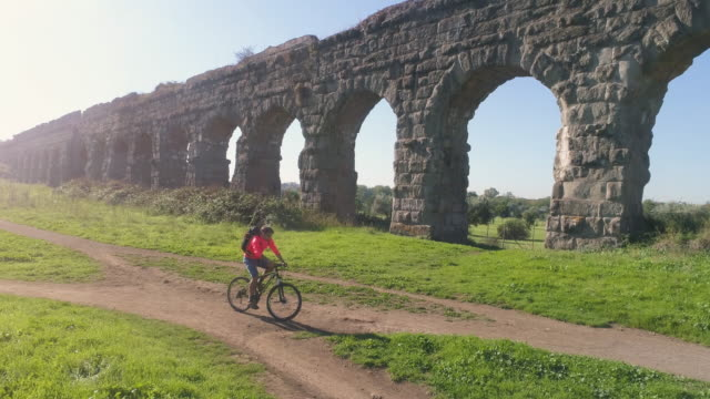 Young man cyclist riding bike on dirt road along ancient roman aqueduct in orange sportswear and backpack aerial view drone dolly video
