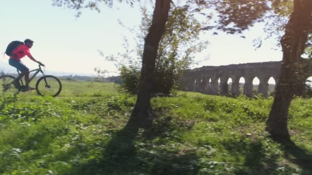 young man cyclist riding bike on dirt road arrives on a hill and stops under a tree in front of ancient roman aqueduct in orange sportswear and backpack aerial view drone dolly - dolly shot video stock e b–roll