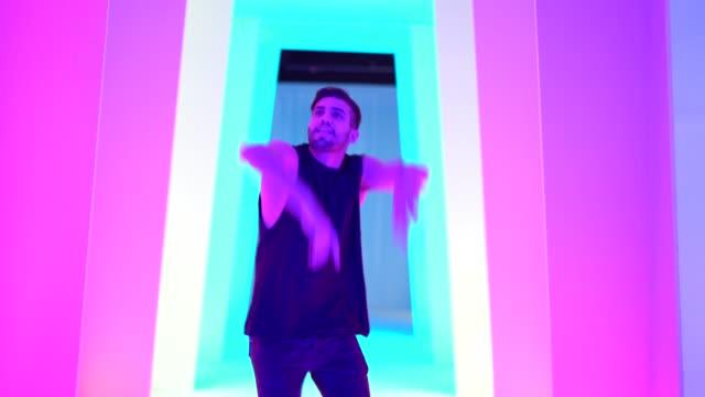 vídeos de stock, filmes e b-roll de jovem dançando no túnel colorido - gênero humano