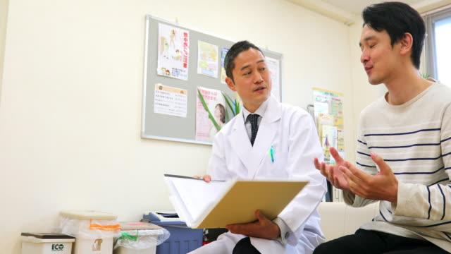 vídeos de stock e filmes b-roll de young man discussing his medical record with a doctor in hospital - exame médico procedimento médico