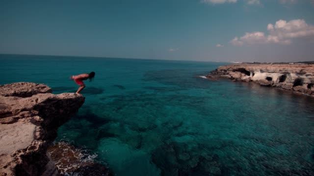 熱帯の島の海の水に崖から飛び込む若者 - 崖点の映像素材/bロール