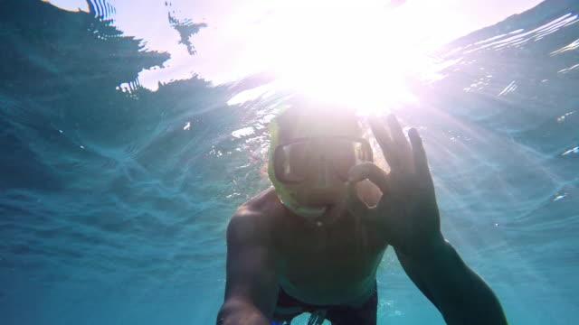POV joven buceando en sol - vídeo