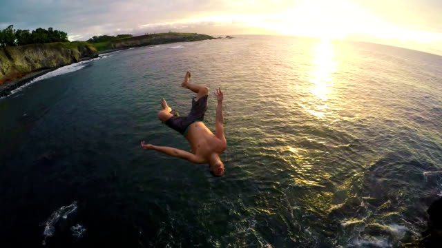 Young Man Does Backflip off Cliff Into Ocean Young Man Does Backflip off Cliff Into Ocean at Sunset. cliff jumping stock videos & royalty-free footage