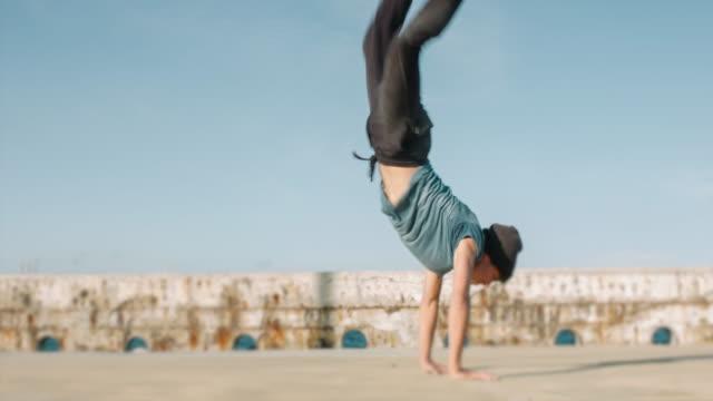 junger mann machen einen handstand acrobat bewegung im freien - stuntman stock-videos und b-roll-filmmaterial