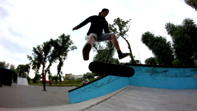 スケートパークでスケート ボードのトリックをやって若い男 - スケートボードをする点の映像素材/bロール