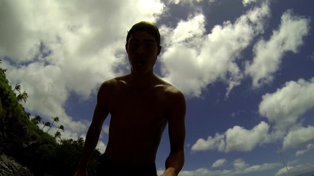 POV Young Man Doing Backflip Into Ocean (Slow Motion) Point of view shot of young man doing backflip into ocean in Hawaii filmed in slow motion.  cliff jumping stock videos & royalty-free footage