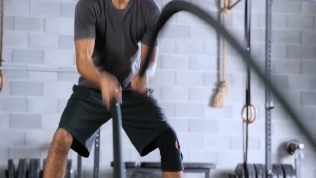 Young man doing battle rope exercise in the gym