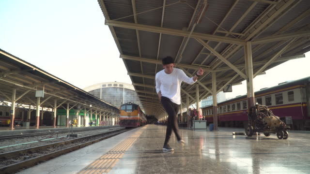 Young man doing breakdance at train station