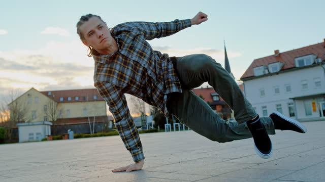 vídeos de stock, filmes e b-roll de jovem fazendo breakdance se move na rua - eslovênia