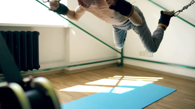 Young man doing exircise on quartering gym equipment and pull his arms and legs with ropes video