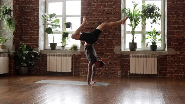 young man doing hand standing pose. guy doing yoga indoors near windows - metodo pilates video stock e b–roll