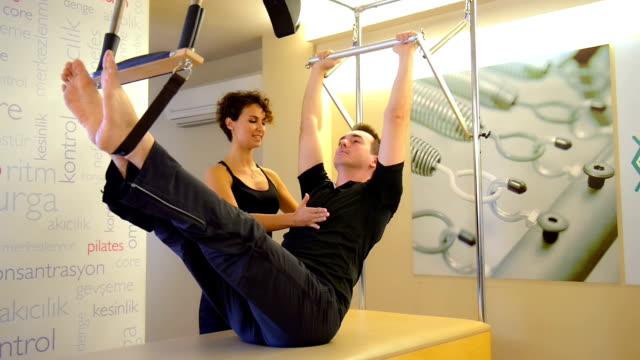dolly: giovane uomo facendo esercizio di pilates con istruttore - metodo pilates video stock e b–roll