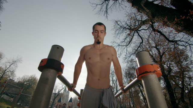 ung man gör armhävningar på ojämna staplar med applåder 4k ultra hd - gymnastikbarr bildbanksvideor och videomaterial från bakom kulisserna