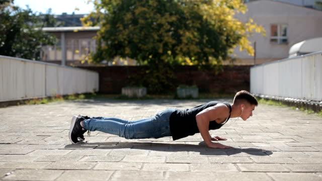 Young man doing push-ups outdoors video