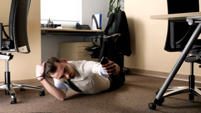 Young man doing selfie lying on the floor in the middle of the office. 60 fps