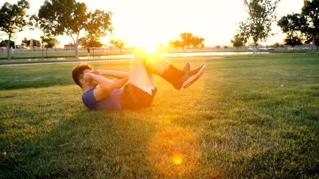 ung man gör situps i parken vid skymning slow motion - djurarm bildbanksvideor och videomaterial från bakom kulisserna