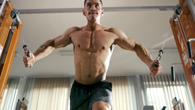 SLO MO Young man doing strength training Slow motion low angle shot of a young man doing strength training in the gym. Shoot in 8K resolution. cross training stock videos & royalty-free footage