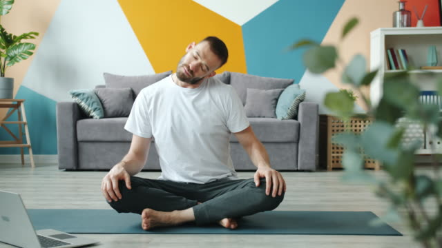 Young man doing yoga at home watching tutorials online on laptop screen Young man doing yoga at home watching tutorials online on laptop screen sitting on mat on laminate floor rotating head warming-up body. People and technology concept. lotus position stock videos & royalty-free footage