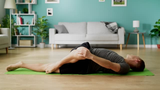 Young man doing yoga in the morning in his living room video