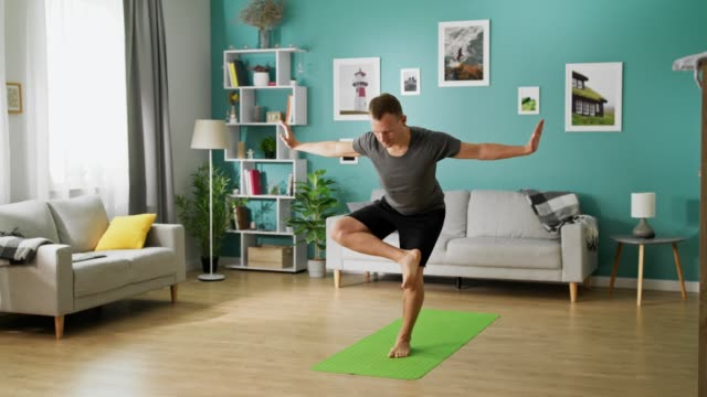 young man doing yoga in the morning in his living room - solo un uomo video stock e b–roll