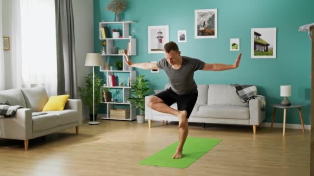ung man gör yoga på morgonen i sitt vardags rum - endast en man bildbanksvideor och videomaterial från bakom kulisserna