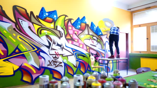 Young man drawing graffiti Young gifted man is drawing graffiti mural in a classroom mural stock videos & royalty-free footage