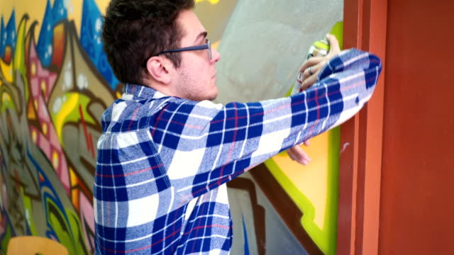 Young man drawing graffiti Young caucasian man with disability drawing a graffiti on a school wall. mural stock videos & royalty-free footage