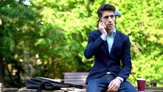 Young man dressed-well answering his phone and taking notes video