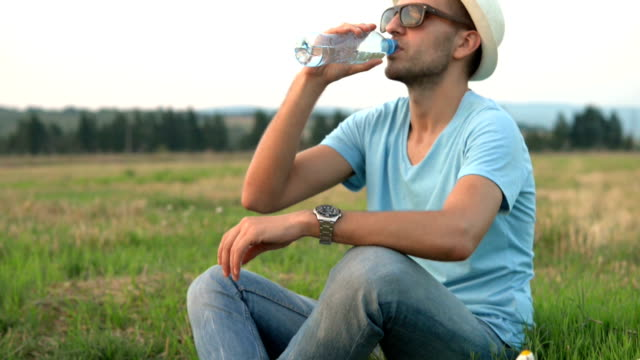 Young man drinking water outdoor video
