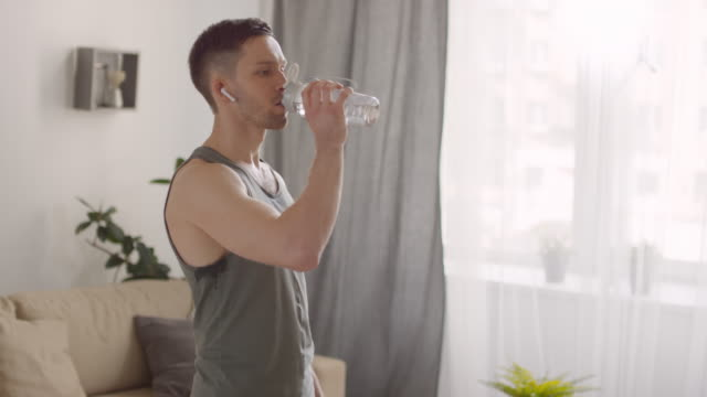 young man drinking water - cuffie wireless video stock e b–roll