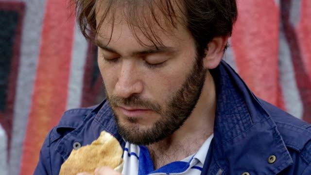 vídeos y material grabado en eventos de stock de joven de comer un sándwich en la calle: composición - largo longitud