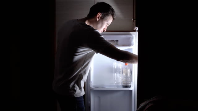 Young man eating at night near the refrigerator Young man eating at night near the refrigerator. snack stock videos & royalty-free footage